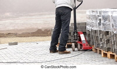handcart carrying heavy paving slabs - worker carries a...