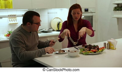 A man with a woman eating chicken and vegetables