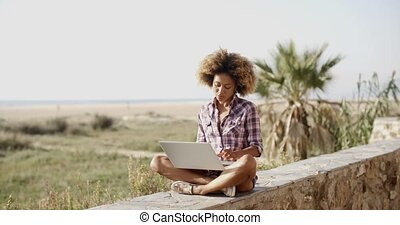 Woman With Laptop Sitting On Stone Wall - Young black woman...