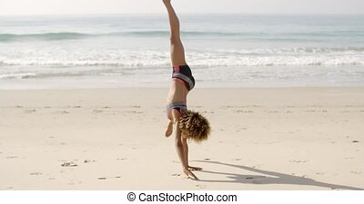 Young Woman Doing Cartwheel On Beach - Young african...