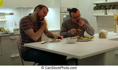 Men eating chicken and vegetables - Men sitting at a table...