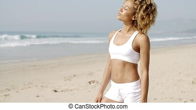 Woman Looking To Camera On The Beach - A young woman looks...