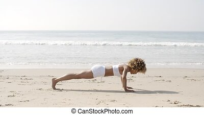 Young Woman Doing Push-Ups On Beach - Fitness young woman...