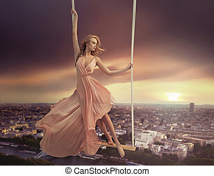 Adorable woman swinging above the city
