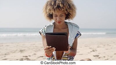 African American Girl Using Tablet Pc At Beach - Pretty...