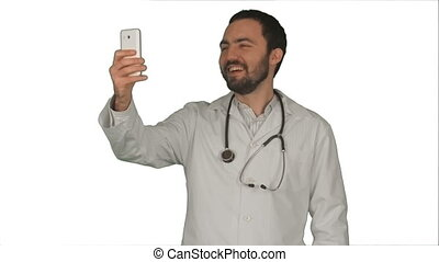 Doctor or medic taking a selfie with front camera of smartphone on white background