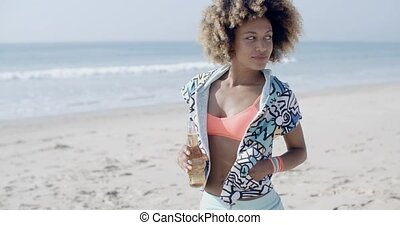 Woman With Bottle Against Sand Beach - Young woman holding...