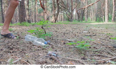 Man beats foot plastic bottle in the forest. - A man stepped...