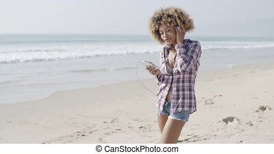 Young Woman Listening To Music At The Beach - Young woman...
