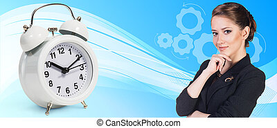 Business woman near classical alarm clock on the blue...