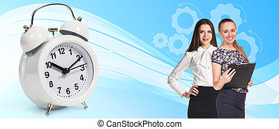 Business women near classical alarm clock on the blue...