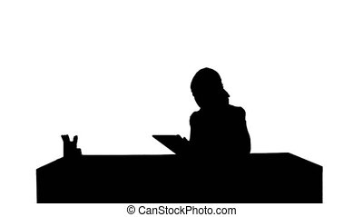 Silhouette Business woman sitting in her office using a tablet computer