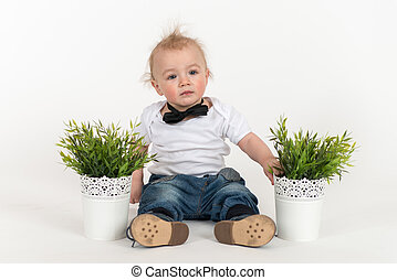 Little boy sits with the plant