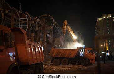 demolition of a small mall at night by hydraulic crashers
