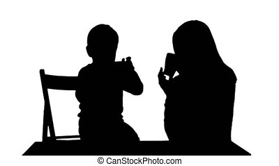 Silhouette Son with his mother drinking tea. Professional...