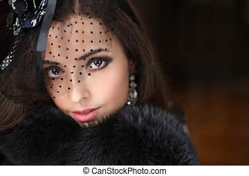 Beautiful fashion retro smiling woman wearing little hat with veil and luxury fur coat, elegant female portrait. Makeup. Jewelry.