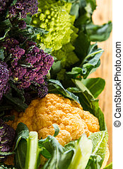 Close up on purple broccoli, with yellow cauliflower and...