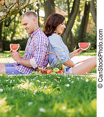 Young family relaxing on a picnic - Beautiful couple leaning...