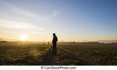 Young man standing on country road in a beautiful landscape looking back