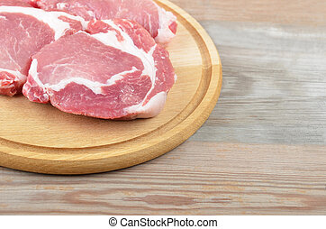 Raw meat steaks on board over wooden background, DOF