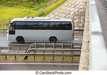 bus goes on highway under bridge - tourist bus goes on...