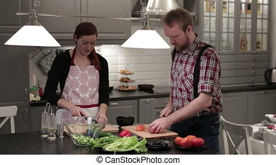 Man and woman cut vegetables on wooden boards - A woman and...