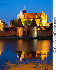 Malbork Castle by night with reflection in Nogat river,...