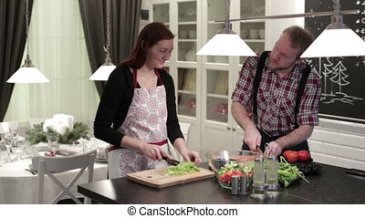 Happy couple cut vegetables on wooden boards