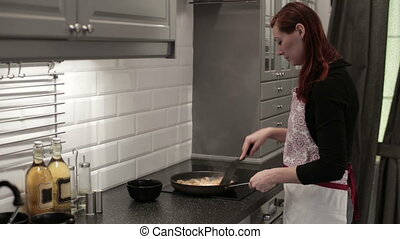 Woman in the kitchen frying shrimp in a pan - The woman in...