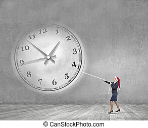 Turn back the time - Woman in Santa hat pulling clock with...