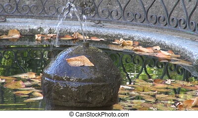 Fountain in autumn park in Madrid - Working fountain with...