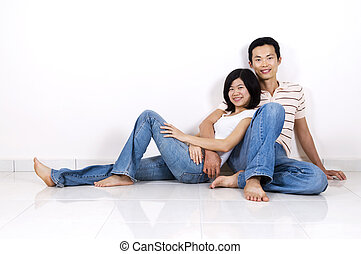 Couple sitting on floor at home - Young Asian adult couple...