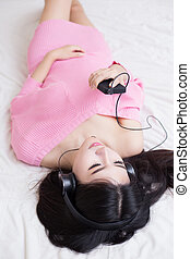 young woman listening music in headphones on her bed