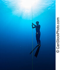 Freediver in the sea - Free diver performing warm up dive -...
