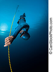 Freediver in the sea - Lady freediver descending along the...