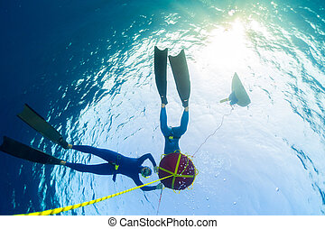 Freedivers in the sea - Freedivers relaxing near the buoy