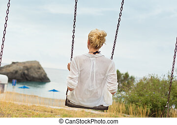 Young blonde woman sitting on the swing on beach.