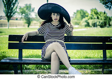 romantic young girl with big black pigeon sitting on a wooden bench in a park in spring
