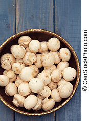 mushrooms in bowl on blue background