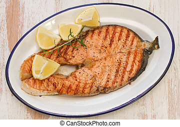 grilled salmon with lemon on dish on white wooden background