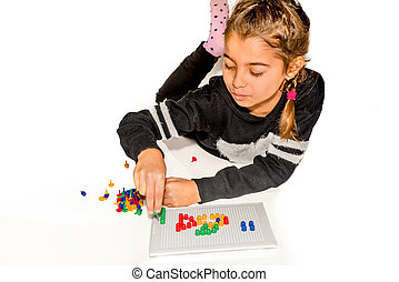 Eight year old girl playing with board game isolated on...