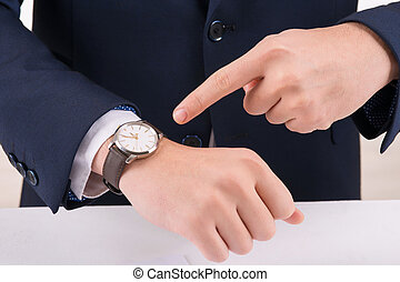 Man pointing at the wristwatch - Time is money Businessman...