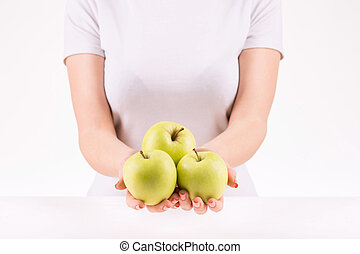 Woman demonstrating three green apples - Organic apples...