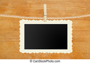 photo paper hanging on rope on wooden background