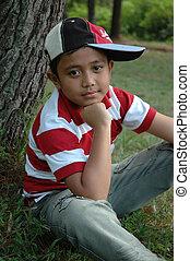 little boy sit down beside pine tree - little asian boy sit...