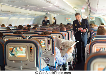 Steward and passengers on commercial airplane - Interior of...
