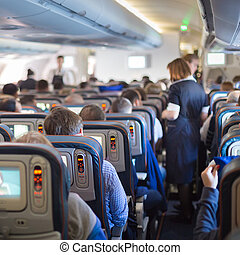 Stewardessand passengers on commercial airplane.