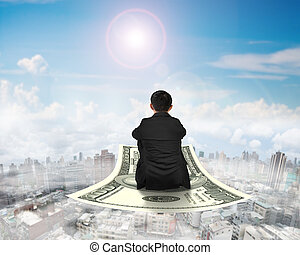 Rear view businessman sitting on money flying carpet
