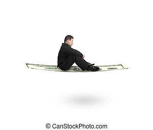 Side view businessman sitting on money flying carpet