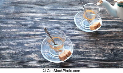 Pouring tea into a cup on a wooden table - Close up detailed...